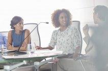 Ritratto di tre donne che discutono al tavolo da conferenza — Foto stock
