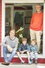 Братья улыбаются с отцом и дедушкой дома — стоковое фото