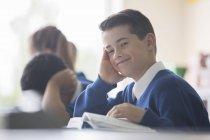 Porträt eines lächelnden Grundschülers am Schreibtisch im Klassenzimmer — Stockfoto