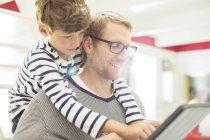 Батько і син, використовуючи цифровий планшетний — стокове фото