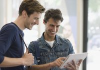 Two male students looking at digital tablet and laughing — Stock Photo
