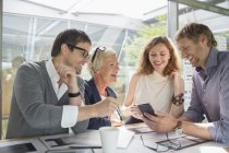 Business people using cell phone in office meeting — Stockfoto