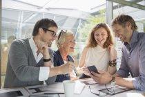 Gens d'affaires à l'aide de téléphone portable en réunion de bureau — Photo de stock