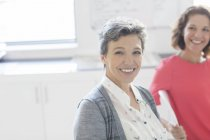 Portrait de souriante femme mature avec une collègue en arrière-plan — Photo de stock