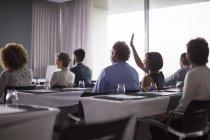 Gruppo medio di partecipanti alla conferenza seduti in sala conferenze con la mano alzata della donna — Foto stock