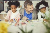 Multi-ethnique père et filles coloriage avec des marqueurs à la table — Photo de stock