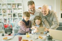 Male gay parents and children video messaging with digital tablet in morning kitchen — Stock Photo