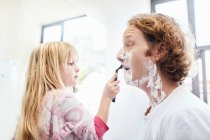 Daughter helping father shave face in bathroom — Stock Photo