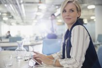 Femme souriante, confiante à l'aide de tablette numérique en réunion de bureau — Photo de stock