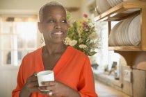 Sorridente il caffè bevente della donna senior in cucina — Foto stock