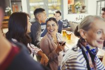 Smiling women friends talking and drinking wine at bar — Stock Photo