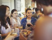 Women friends talking and drinking beer and wine at bar — Stock Photo