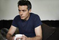 Uomo seduto sul divano tenendo tazza cercando triste — Foto stock