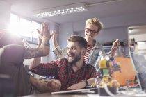 Concepteurs enthousiastes haute-cinq, célébrer dans l'atelier — Photo de stock