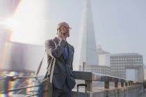 Businessman talking on cell phone on bridge, London, UK — Stock Photo