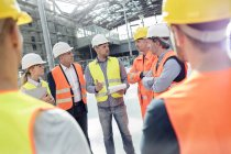 Foreman, engineers and construction workers meeting at construction site — Stock Photo