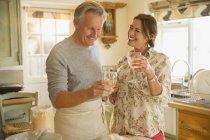 Улыбающаяся зрелая пара пьет вино и готовит на кухне — стоковое фото