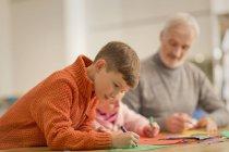 Мальчик рисует, делает ремесла с семьей за столом — стоковое фото