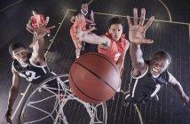 Молодые баскетболисты, прыгающие на баскетбол в сетку на баскетбольной площадке — стоковое фото