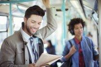 Businessman reading newspaper on train — Stock Photo