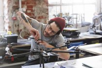 Male designer with tattoos assembling drone in workshop — Stock Photo