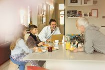 Maschi gay genitori e bambini che godono di colazione al bancone della cucina — Foto stock