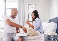 Smiling couple drinking coffee in bed — Stock Photo