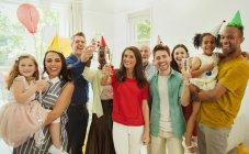 Retrato entusiasmado multi-étnico multi-geração da família festa comemorativa com champanhe e chapéus de festa — Fotografia de Stock