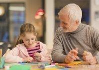 Padre e figlia bonding, facendo mestieri al tavolo — Foto stock