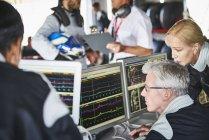 Equipe de Fórmula 1 revisando dados de telemetria de diagnósticos em computadores — Fotografia de Stock
