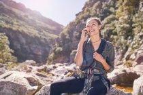 Giovane donna che parla sul cellulare sotto sole, scogliere scoscese — Foto stock