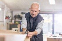 Focused senior male carpenter using jack plane on wood boat in workshop — Stock Photo