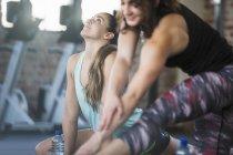 Junge Frauen, die Dehnung Übung zur Vorlesung im Fitnessstudio — Stockfoto