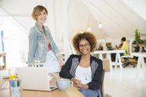 Portrait de femmes souriant au bureau avec ordinateur portable sur le bureau — Photo de stock