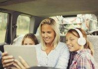 Mère et filles regarder la vidéo sur tablette numérique sur la banquette arrière de voiture — Photo de stock