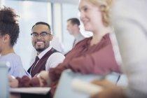 Uomo d'affari sorridente ascolto in pubblico Conferenza — Foto stock