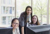 Portrait confiant, souriant enseignante et les filles étudiantes de recherche à l'ordinateur dans la bibliothèque — Photo de stock
