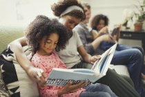 Parents reading books with daughters on living room sofa — Stock Photo