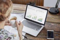 Empresaria bebiendo té y revisando datos en el portátil - foto de stock