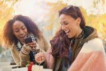 Молодая женщина с камеры телефона фотографирование друга едят Чизкейк-десерт на тротуаре кафе — стоковое фото