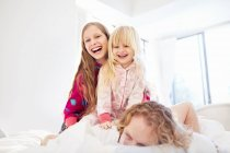 Laughing sisters on top of father on bed — Stock Photo