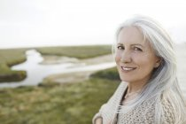 Портрет улыбающейся пожилой женщины на пляже — стоковое фото
