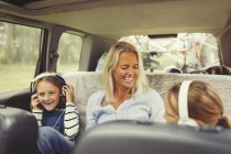 Laughing mother and daughters with headphones in back seat of car — Stock Photo