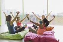 Mujeres apoyadas con los brazos levantados sobre cojines en el gimnasio de clase de ejercicio - foto de stock