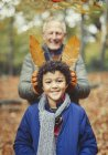 Grandfather holding autumn leaves behind grandson in woods — Stock Photo