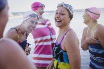 Улыбающиеся женщина активный пловцов с полотенца в отеле ocean на открытом воздухе — стоковое фото