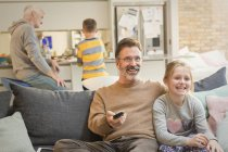Male gay parents watching TV and bonding with children — Stock Photo