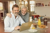 Male gay couple using laptop and eating breakfast at kitchen counter — Stock Photo