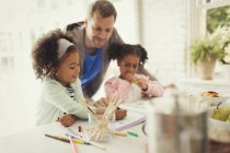 Multi-ethnic father and daughters coloring together — Stock Photo