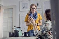 Mujeres fotógrafas hablando, reuniéndose en la oficina - foto de stock
